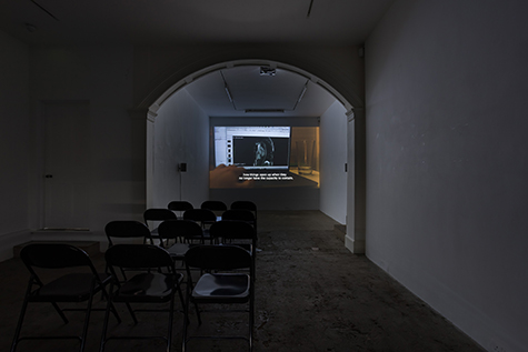 A film is projected in a dark art gallery. The projection shows a black-and-white medical image of the inside of a body displayed on a computer screen. A hand reaches toward the computer. Over the projected image, a caption reads - how things open up when they no longer have the capacity to contain. The projection is framed by an archway; the room is set up with rows of folding chairs.