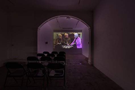 A film is projected in a dark art gallery. The projection shows three elderly white women seated together. Two of the women are wearing leopard print and have strawberry blonde hair, looking at the third woman with seeming concern. The third woman is wearing a pink track jacket and has white hair; she appears to be explaining something. Over the projected image, a caption reads - Two of the sisters dress alike all the time. The projection is framed by an archway, which is lit pink by the image; the room is set up with rows of folding chairs.