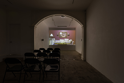 A film is projected in a dark art gallery. The projection shows a purple sofa with plaid decorative pillows in slight disarray in front of a magenta wall. Above the sofa, a painting of a lush private garden hangs, flanked on either side by two pedestals displaying porcelain figurines. Next to the sofa, a table displays black and white photos and a lamp. Over the projected image a caption reads- (Jordan) A lavender sofa is shown. The projection is framed by an archway; the room is set up with rows of folding chairs.