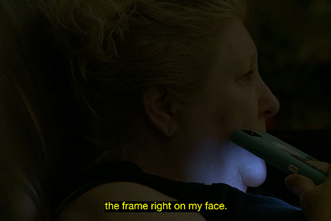 Another scene from the film shown in the previous image, shows a close-up of a woman's face in low light. She holds a mobile phone to her cheek, with the screen facing down and lighting her chin and neck. Over the image a caption reads - the frame right on my face.